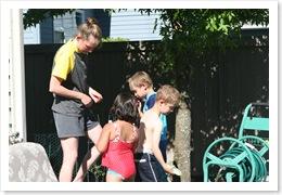 Tammi (esposa do chefão) e crianças enchendo balões d'água
